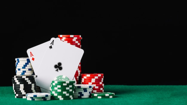 Stack of white; green; black and red casino chips with two aces on poker table Free Photo