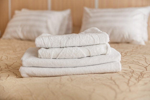 Stack of white hotel towel on bed in bedroom interior. Premium Photo