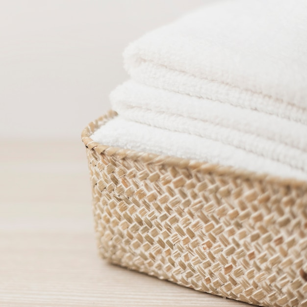 Stack of white towels in basket Free Photo