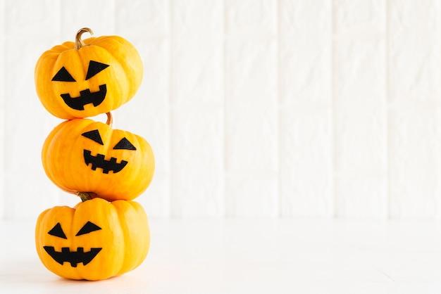 Stack of yellow ghost pumpkin on white brick block background Premium Photo