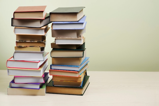 stacked books of different colors and sizes photo free download