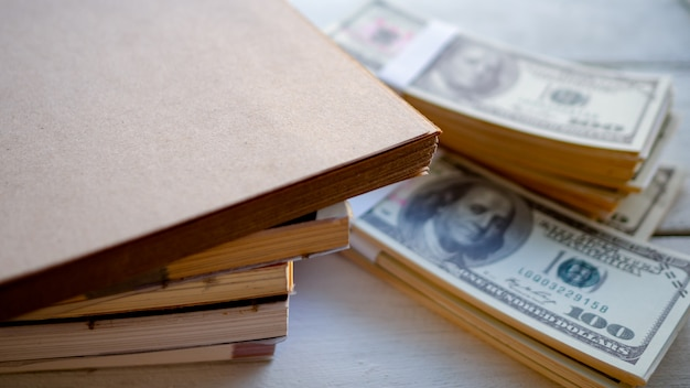 Stacked books with dollar money placed on the table Premium Photo