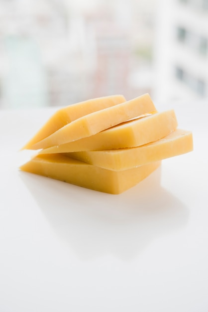Stacked of cheese slices on white table Free Photo