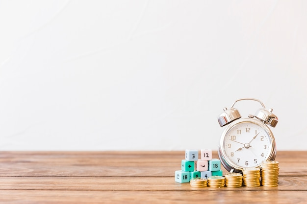 Stacked coins, alarm clock and math blocks on wooden surface Free Photo