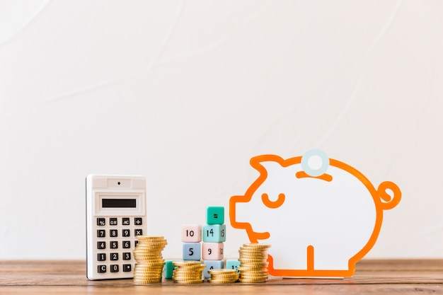 Stacked coins, math blocks, calculator and piggybank on wooden tabletop Free Photo