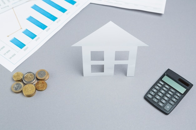 Stacked coins and paper cutout of house with calculator on business desk Free Photo