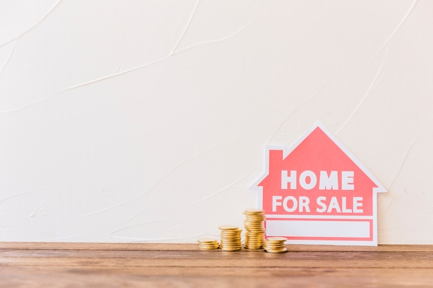 Stacked coins with home for sale icon leaning on wall Free Photo
