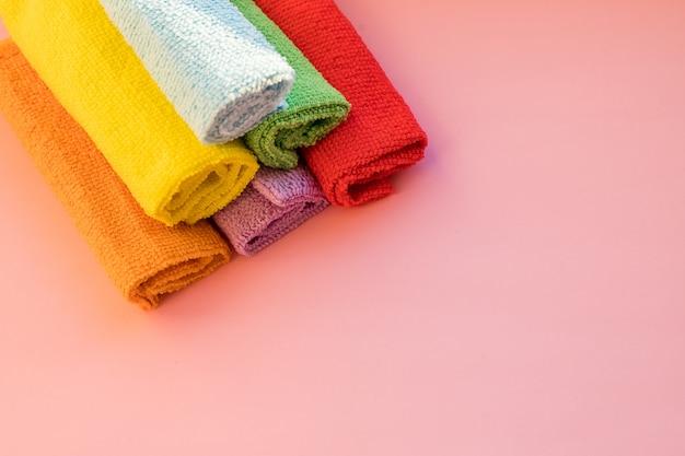 Штабелированные красочные салфетки из микрофибры на розовом фоне. сухие салфетки из микрофибры для чистки различных поверхностей на кухне. скопируйте место для текста или логотипа. Premium Фотографии