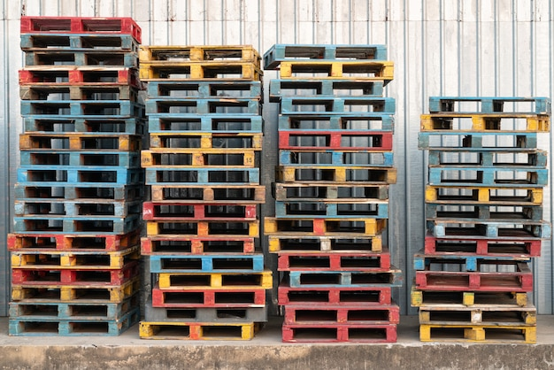 Stacked of colorful rough wooden pallets background at warehouse