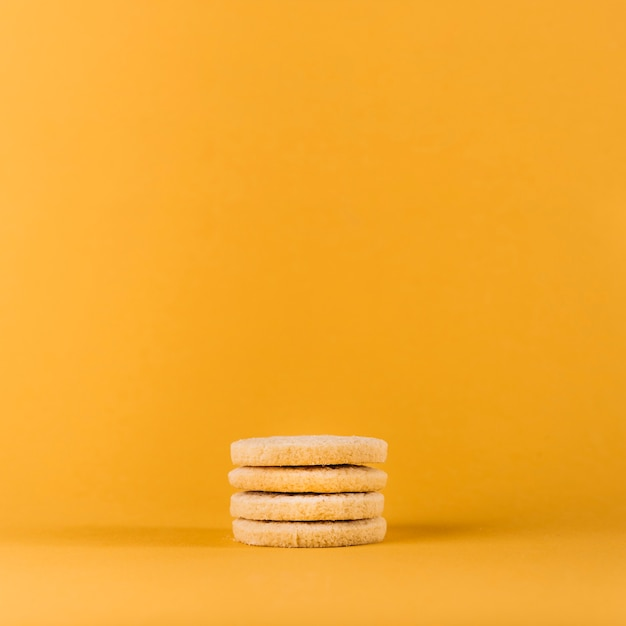 Stacked cookies on yellow background Free Photo