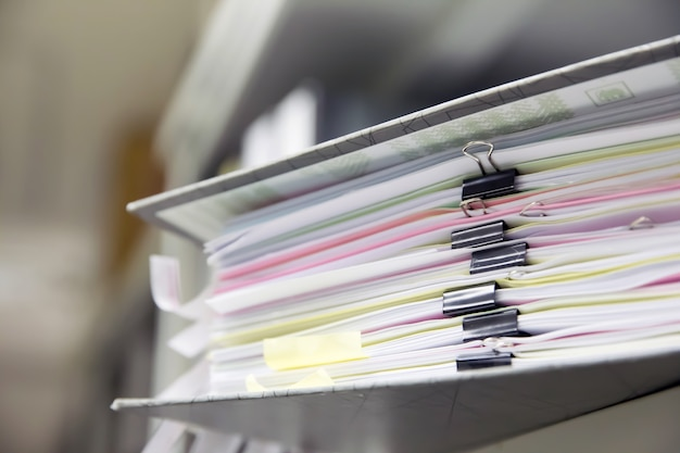 Stacked document files with  black paper clip on shelves. Premium Photo