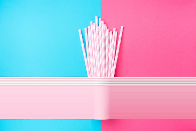 Stacked drinking paper cups with striped straws on duo tone blue pink background. Premium Photo