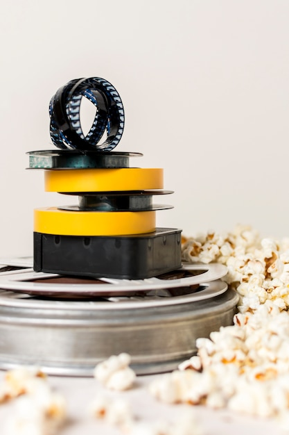 Stacked of film reels with film strip near the popcorn against white background Free Photo