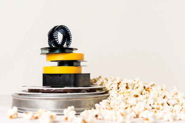 Stacked of film reels with film strip on top near the popcorn against white background Free Photo
