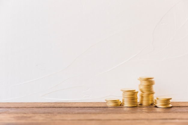 Stacked golden coins in front of wall Free Photo