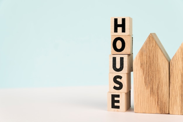 Stacked of letter house blocks near the house model against blue background Free Photo