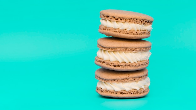 Stacked of macaroons on turquoise background Free Photo