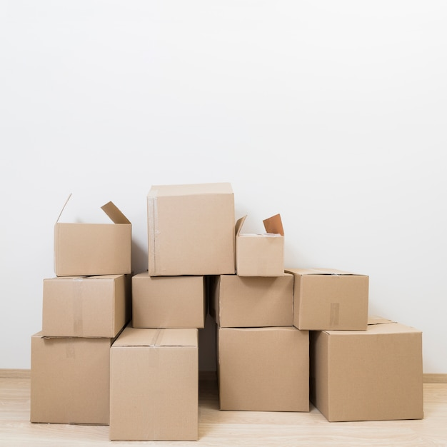 Stacked of moving cardboard boxes against white wall Free Photo