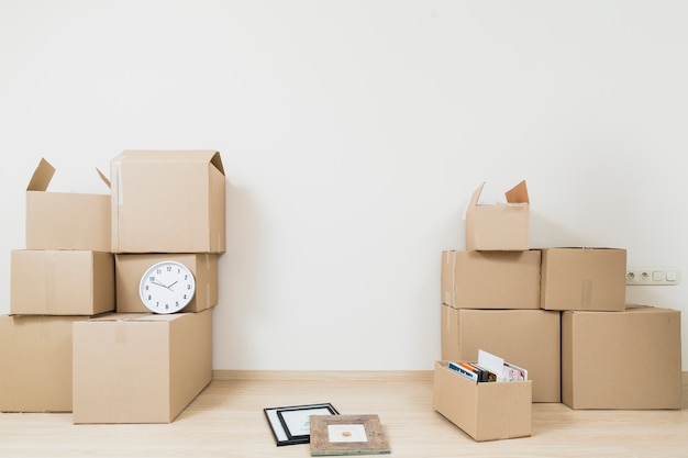 Stacked of moving cardboard boxes with clock and picture frame against white wall Free Photo
