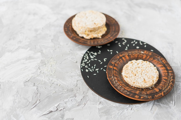 Stacked of puffed rice cake with grains on white textured background Free Photo