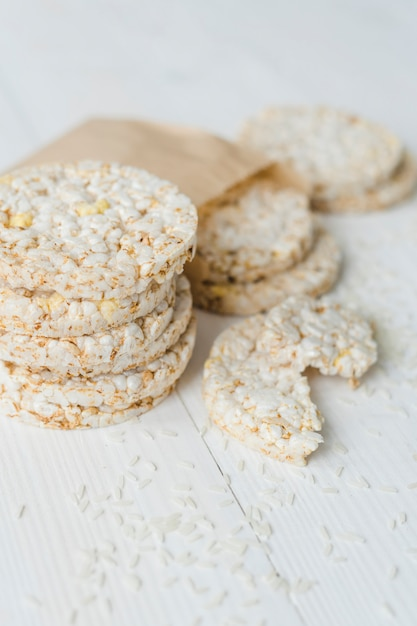 Stacked of puffed rice with grains on white wooden table Free Photo