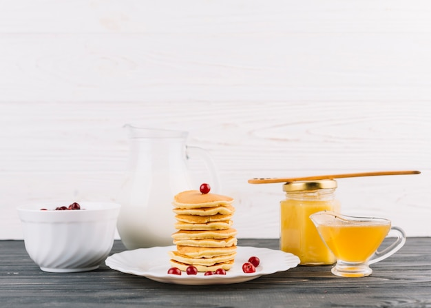 Stacked of small pancakes with red currant berries and lemon curd against white wall Free Photo