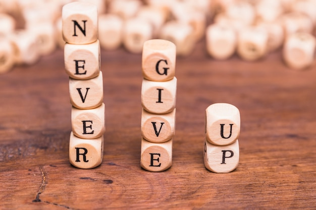 Stacked of wooden blocks with word never give up on wooden desk Free Photo