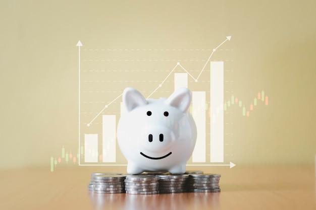 스택 동전 더미와 돈으로 저축을위한 흰색 돼지 저금통 및 계획 단계는 비즈니스 그래프 배경으로 성장하고 퇴직 기금 및 미래 계획 개념에 대한 비용을 절약합니다. 프리미엄 사진
