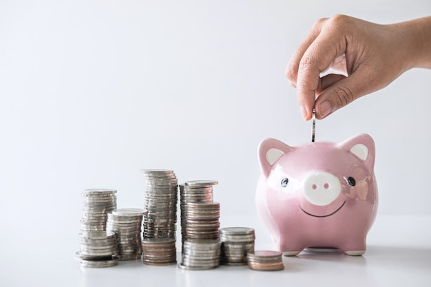 Stacking pile and hand putting coin into piggy bank for planning step up to growing Premium Photo