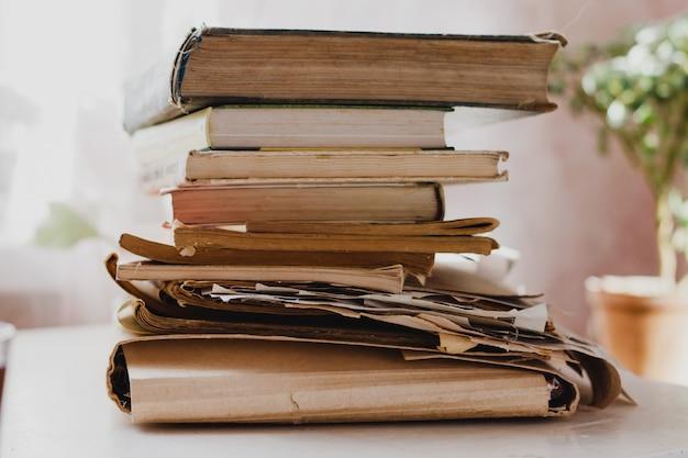 Стопки книг и газет на белом столе в светлой комнате. книги в библиотеке, архив данных, записи. концепция всемирного дня книги Premium Фотографии
