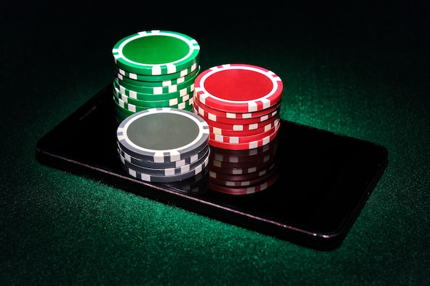 スマートフォンのカジノチップのスタック、緑のフェルトポーカーテーブルの背景。オンラインゲームのコンセプト。 Premium写真