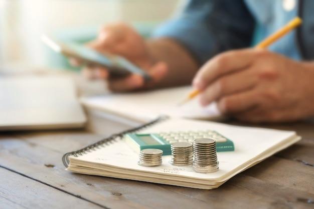 Стеки монет на деревянном столе с калькулятором. налогообложение, домашний бухгалтерский учет или кредитный анализ для концепции оплаты ипотеки Premium Фотографии