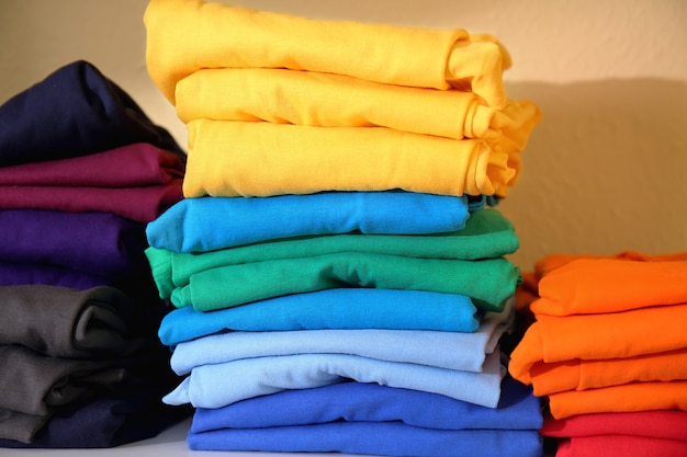 선반에 인쇄하기 위해 준비된 다채로운 티셔츠 더미 프리미엄 사진