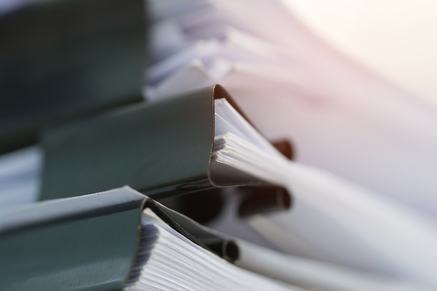 stacks of paper files on desk for report or piles of unfinished