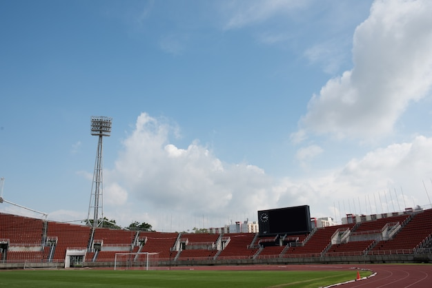 Stadium background with a green grass pitch in the daytime Free Photo