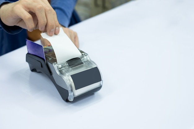 Staff cashier rip bill paper with card on payment terminal Premium Photo