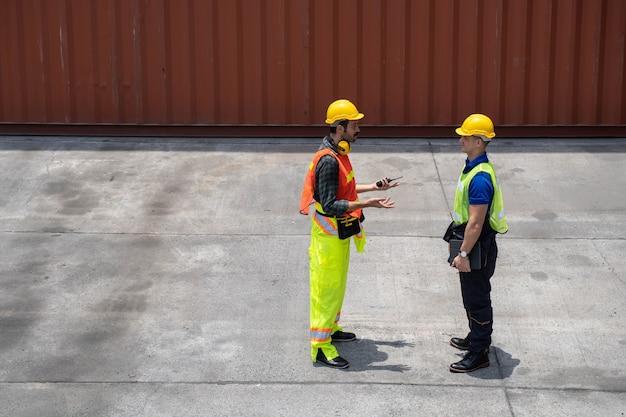 수출입을 위해 화물선에서 컨테이너 상자를 서서 확인하는 직원 프리미엄 사진