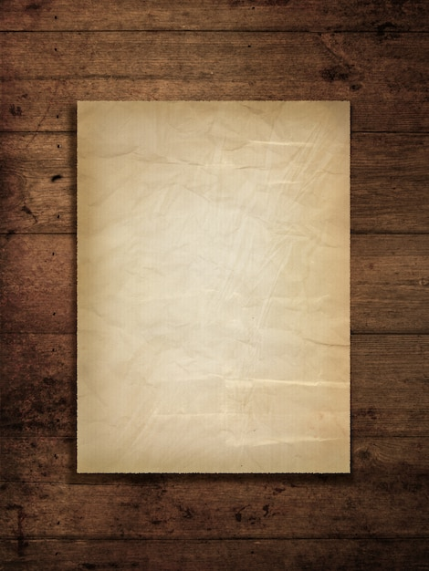 Stained old paper on a grunge wood background Free Photo