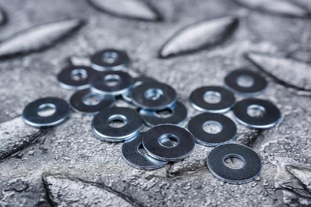 Шайбы для выращивания из нержавеющей стали, металлический крепеж, многие шайбы для строительства в качестве фона в промышленном стиле, крупный план Premium Фотографии