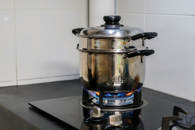 A stainless steel pot is placed on a gas stove. Premium Photo