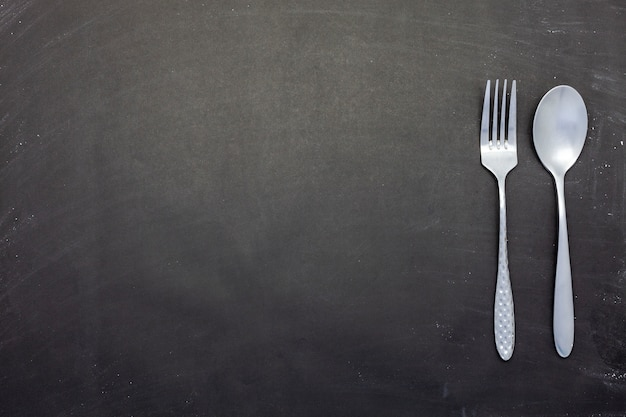 Stainless steel spoon and fork on black wood or chalkboard background with copyspace Premium Photo