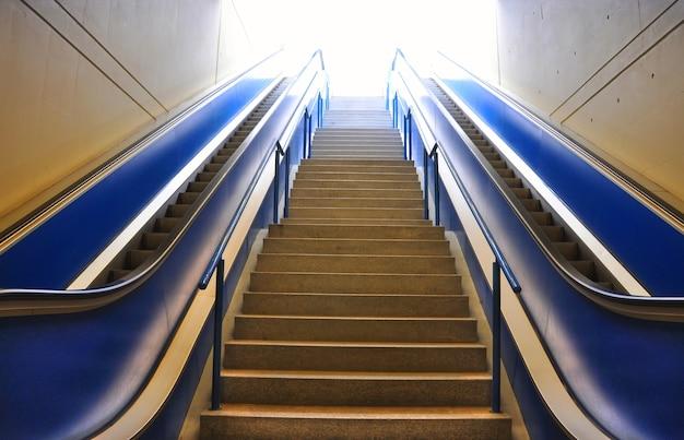 건물의 조명 아래 계단과 두 개의 에스컬레이터 무료 사진