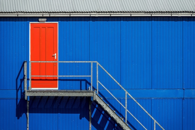 빨간 문으로 이어지는 차고의 파란색 벽 근처 계단 무료 사진