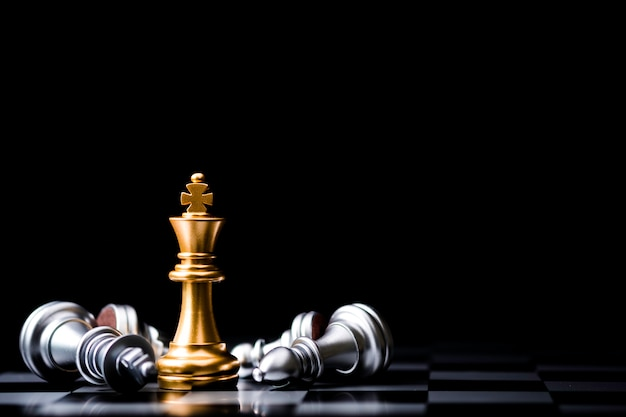 Stand of golden king chess and fallen silver king chess. winner of business competition and marketing strategy planing concept. Premium Photo