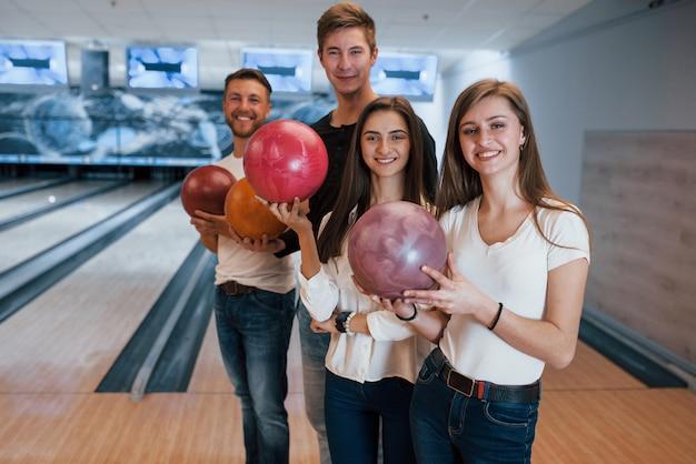 In piedi contro l'area di gioco. i giovani amici allegri si divertono al bowling durante i fine settimana Foto Gratuite