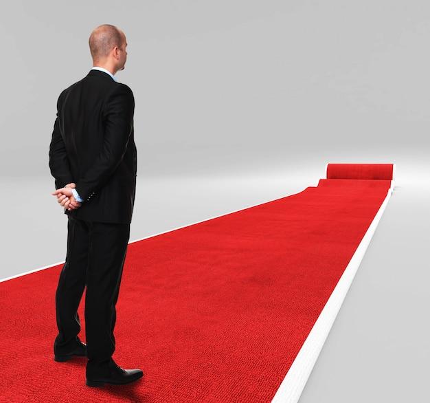 Standing businessman on red carpet Premium Photo