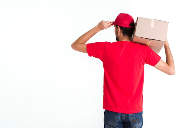 Standing courier man holding box and cap from the back shot Free Photo