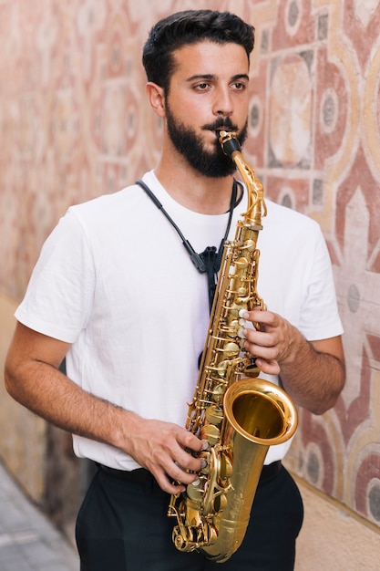 Standing man playing the saxophone with geometric background Free Photo