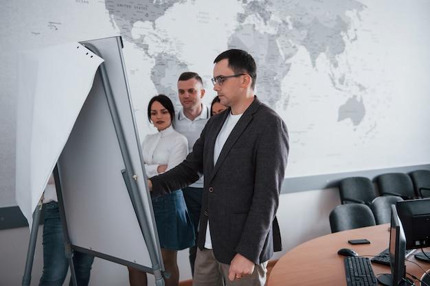 In piedi vicino alla lavagna. uomini d'affari e manager che lavorano al loro nuovo progetto in classe Foto Gratuite