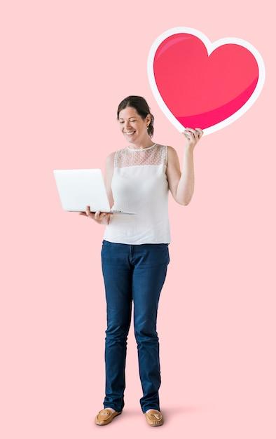 Стоящая женщина держит сердце смайлик и ноутбук Бесплатные Фотографии